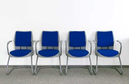 row: Four Blue chairs in simple empty waiting room