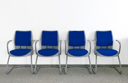 sedia vuota: Quattro sedie blu in semplice stanza vuota in attesa