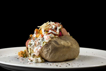 spud: Stuffed baked potato on plate isolated on black background