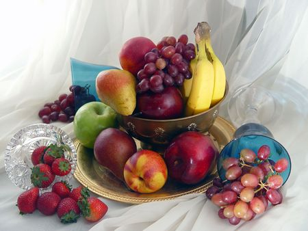 Brass bowl overflowing with grapes, nectarines, apples, pears, bananas, strawberries and grapes. Stock Photo - 572950