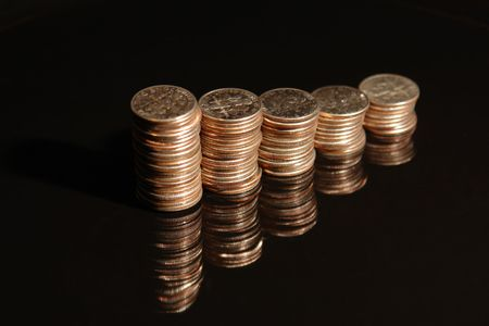 penny pinching: Stacks of dimes against a black background