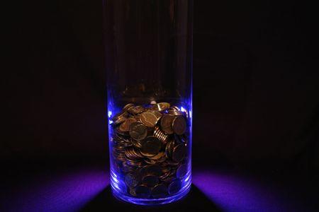 Jar of coins in blue on black.