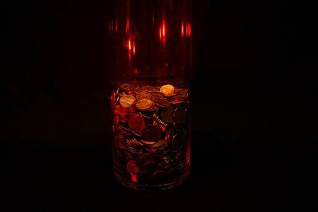 Jar of coins against a black background.