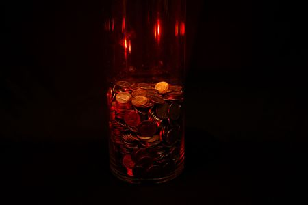 penny pinching: Jar of coins against a black background.