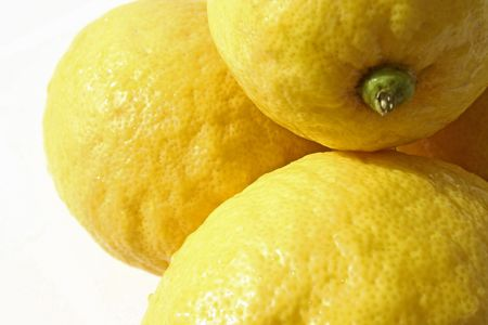 fresh wet yellow lemons laying in the sun against white backgound Stock Photo