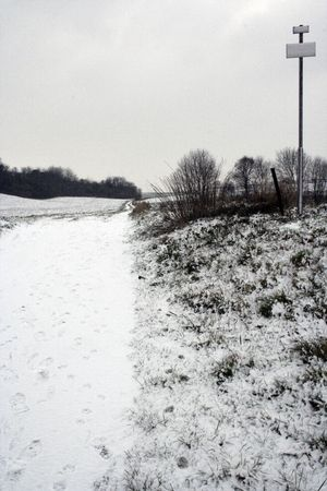 another road in wintertime with sign