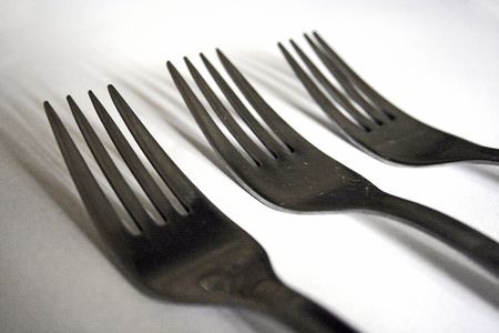 three forks laying on white background Stock Photo