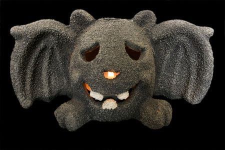 halloween bat with lit candle on black background