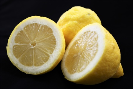 sourness: two lemons against black background Stock Photo