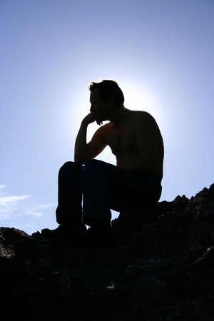denker: silhouet van een man zittend op rots met zon Stockfoto