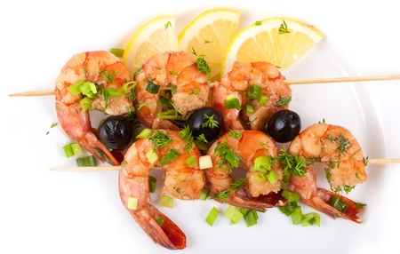 Barbecue with Tiger Prawns on a Skewer with Olives and Lemon on white Background photo