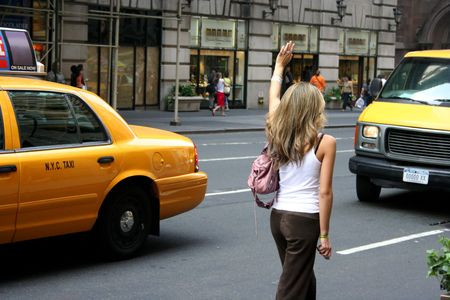 A young woman standing on a street, trying to catch (hailing) a cab. Manhattan, NYC photo