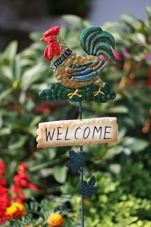 neighborly: welcome sign with rooster closeup in garden. Stock Photo