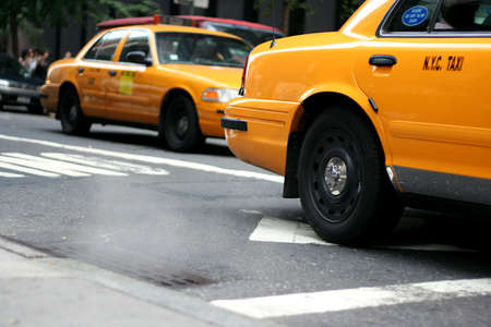 catching taxi: Taxi driving by a steaming manhole in New York City Stock Photo