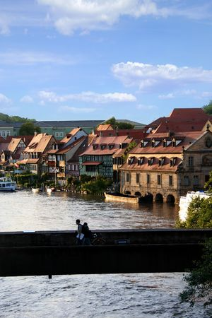 middle ages boat: Silhouette of a stone bridge over a river in the medieval city of Bamberg in Bavaria, Germany with great lighting of the sun Stock Photo