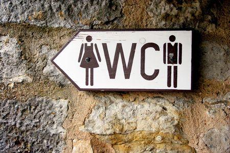 meados: Hombres y mujeres aseo  ba�o p�blico de madera se�al que apunta a la izquierda sobre un muro de piedra