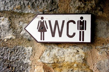 water closet: male and female toilet  public restroom wooden sign pointing to the left on a stone wall Stock Photo