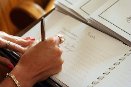 wedding guest: Womans hand signing a guest book with a pen