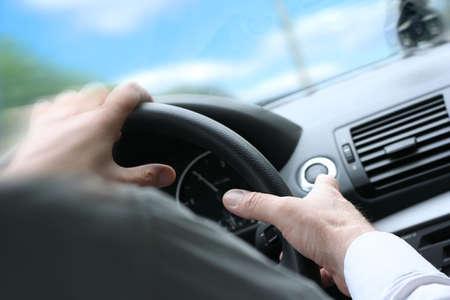 hombre manejando: M�s de hombro vista de un hombre conducir un autom�vil con las manos en el volante, giro r�pido. (soleado)  Foto de archivo