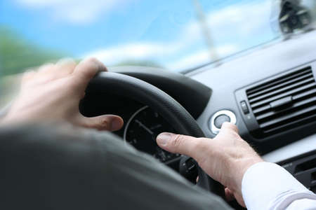 Over shoulder view of a man driving a car with his hands on the steering wheel, turning quick. (sunny weather) photo