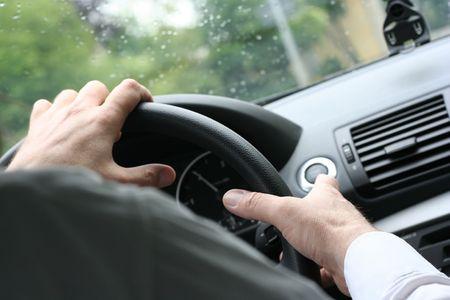 hombre conduciendo: M�s de hombro vista de un hombre conducir un autom�vil con las manos en el volante. (Tiempo lluvioso)