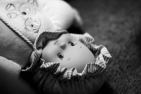 left behind: Close-up of doll left behind laying on the floor unattended. High contrast grainy black and white picture with narrow depth of field and copy space on the top-right.