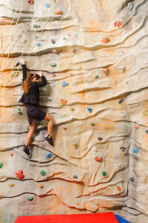 manmade: Businesswoman climbing on man-made cliff in the sport centre