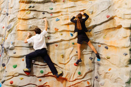 manmade: Competition between business partners on man-made cliff in the sport centre Stock Photo