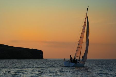 bateau voile: Le yacht pr�s de l'�le. L'or du ciel. Le gagnant. Une vague de la main. Il est un succ�s Banque d'images
