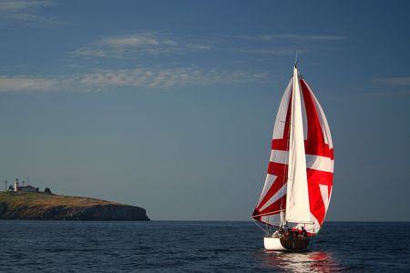 The Yacht with a red sail near island. photo