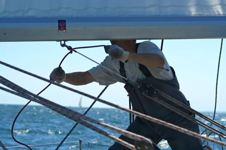 Sails is a man's work. One the man works with sails and cords. Stock Photo - 474020