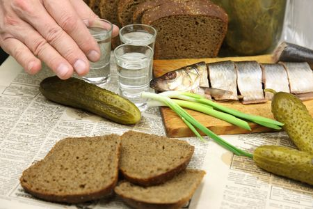 Vodka, herring, pickles, black bread on the tablecloth from the newspaper. Three hands are stemware, clink glasses, drink and a snack.   photo