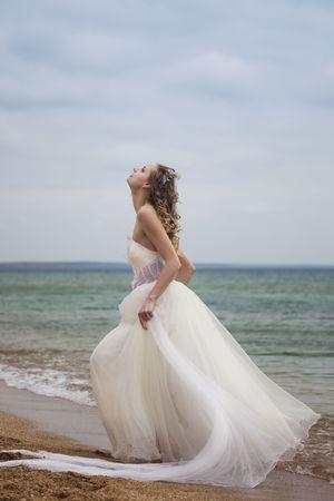 beautiful bride  dancing on the beach photo