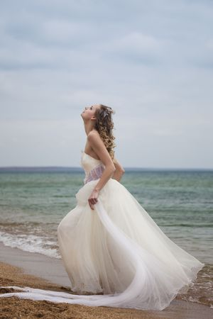 traditional   dress: beautiful bride  dancing on the beach Stock Photo