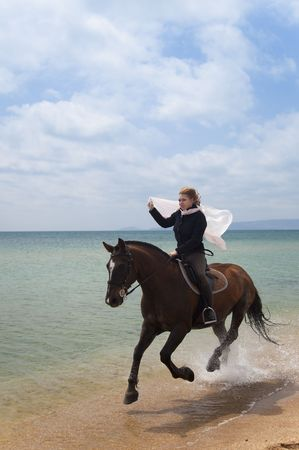 Girl on a horse galloping along the beach photo