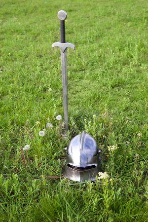 broadsword: sword and helmet on the green grass