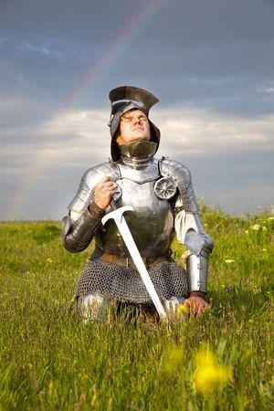 cavaliere medievale: cavaliere stanco, dopo la battaglia  pioggia e reale arcobaleno