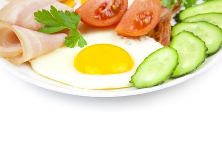 fried eggs with bacon and vegetables  on white background photo