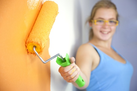 Happy young woman painting wall  Color your life  focus on the roller photo