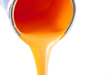 paintcan: orange paint flows from the bucket  isolated on white with copy space  photo Stock Photo