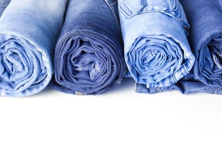 tienda de ropa: Rollos de pantalones vaqueros aislados en fondo blanco con espacio de copia para el texto Foto de archivo