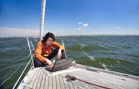 sailboats: Businessman with laptop computer on sailboat