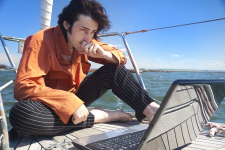Businessman with laptop computer on sailboat photo
