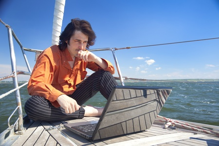 adult cruise: Businessman with laptop computer on sailboat
