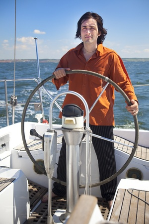 Young  skipper driving sailboat  Captain of the yacht photo
