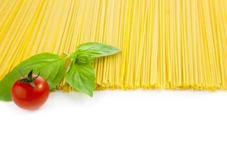 Italian cooking spaghetti with tomatoes and basil  isolated on white  photo