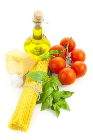 Ingredients for Italian cooking: olive oil, basil, tomato, parmesan, garlic and spaghetti   isolated on white photo