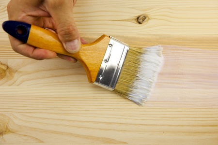 Wood texture, hand and paintbrush  covering by varnish photo