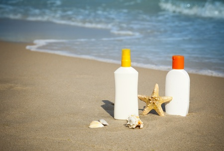 Suntan Lotion Flacons on the Beach with copy space  photo