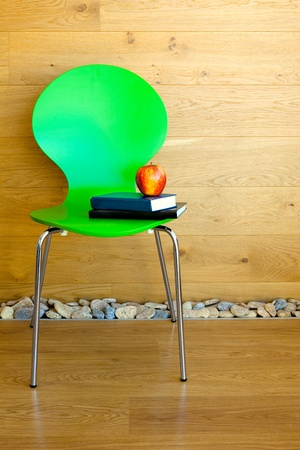 Green Chair, Red Apple and some Books against wooden wall  Modern interior photo